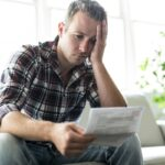 Shocked man holding some documents on sofa livingroom